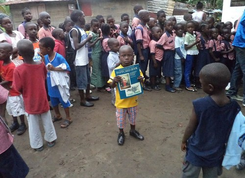A child displays his book; others wait for theirs