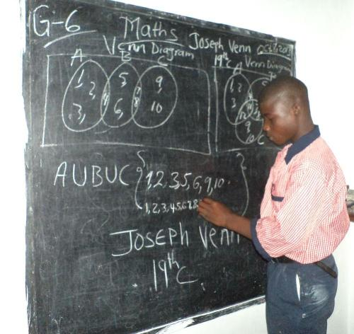 Student Jomo Peters practicing his maths on the chalkboard