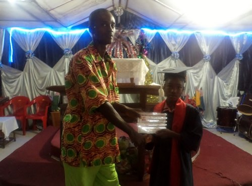 The Principal, Mr. Varney Gibson, issuing a certificate to one of the graduates