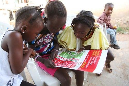 Girls reading Ebola awareness poster (Photo: UNICEF)