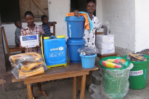 L-R: The Registrar (Miss Annie Dayugar) and the Principal (Mr. Varney Gibson) posing behind the donated items