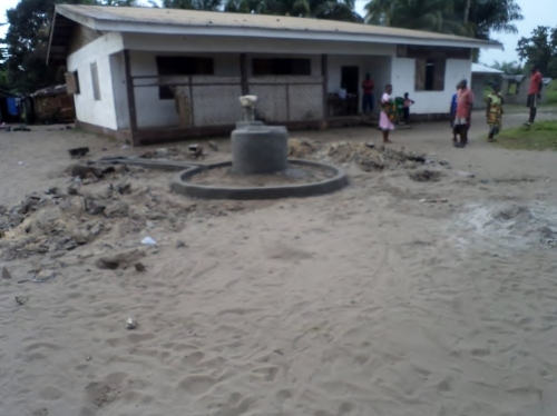 A photo showing the position of the hand pump in front of the school building