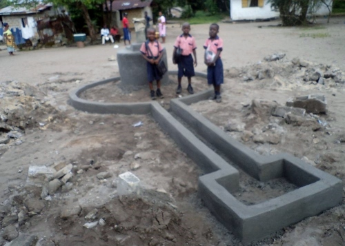 Three kindergarten kids posing at the newly renovated hand pump