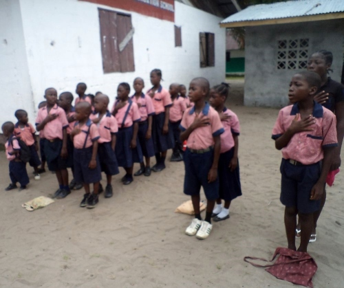 Students singing the National Anthem during devotion