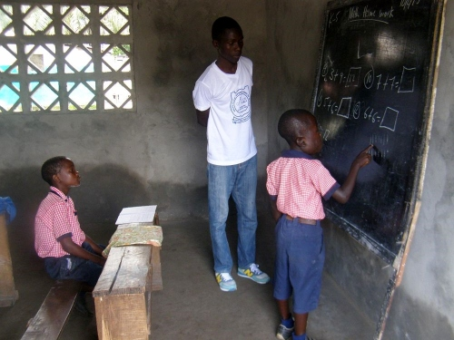 A K-4 student doing mathematics on the blackboard