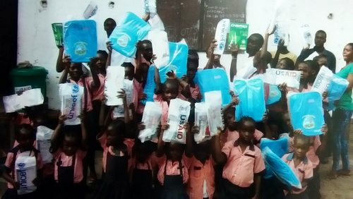 Students displaying their donated book bags and copybooks