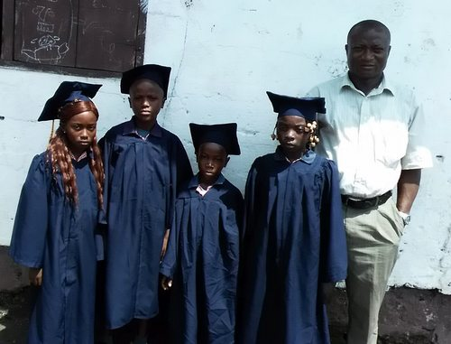 The school's Director, Paul Yeenie Harry, posing with the graduates