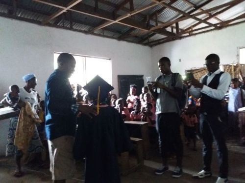 P-T.A chairman certificating one of the graduating kids, as parents take pictures